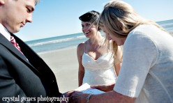 the bride and groom sign their marriage license after their wedding on folly beach